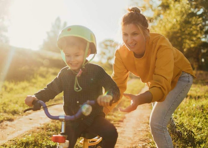 mom teaching son to ride a bike