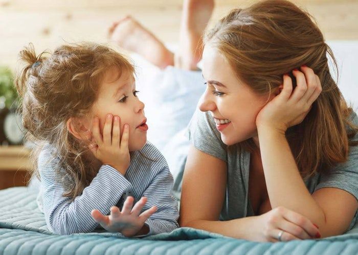 Happy mom and daughter on bed.