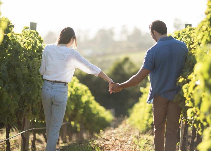 Couple walking through a vineyard.