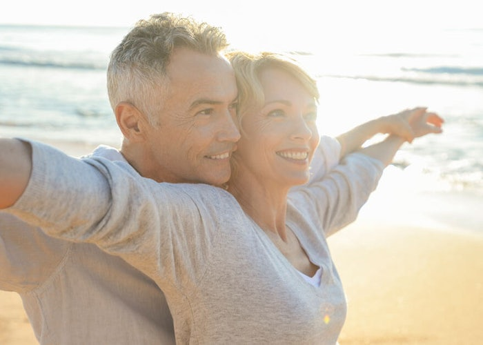 Happy older couple on the beach at sunrise.