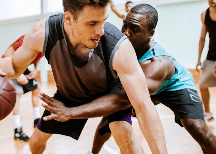 Men playing basketball at local gym.